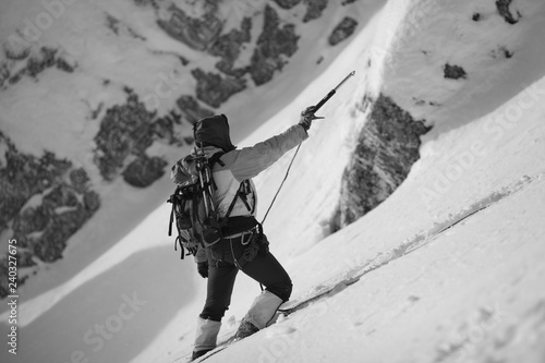 Poster de jardin Alpinisme A climber on a snowy slope holds an ice ax in his hand, marking the path between the rocks. Black and white.