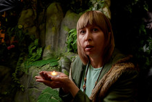 Girl In A Green Jacket With Blond Hair With A Small Candle In Her Hands Near An Artificial Rock With A Grotto