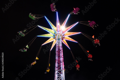 Colorful neon swinging carousel ride at night at the San Diego County Fair in Ca Fototapeta