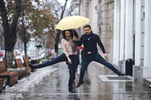 Happy Couple, Guy And His Girlfriend Dressed In Casual Clothes Are Jumping Under The Umbrella On The Street In The Rain.