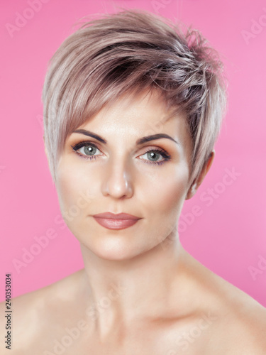 Portrait of a beautiful blonde woman with beautiful make-up and short haircut after dyeing hair in a hairdressing salon on a pink background.