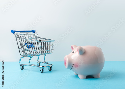 Obraz na plátne  Piggy bank with shopping cart on blue table