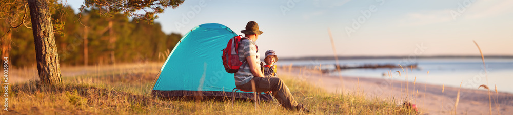 Fototapeta Family resting with tent in nature at sunset