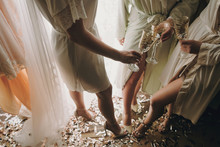 Bride With Bridesmaids In Silk Robes Toasting With Champagne Glasses And Showing Sexy Legs, Standing On Gold And Silver Confetti,bridal Boudoir Morning Party. Hen Shower.