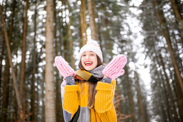 FototapetaPortrait of a young woman dressed in bright winter clothes standing in pine forest during the winter time