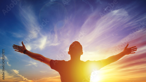 Fototapeta Young man standing outstretched at sunset. Bright solar glow and sky obraz