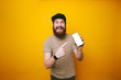 Happy young bearded man is pointing at white screen of smartphone