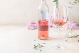 Glass and bottle of rose wine on light background. - 240377283
