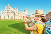 Happy Female Traveler In Hat With Backpack Taking Photo Of The Leaning Tower In Pisa. Vacation And Lifestyle Concept
