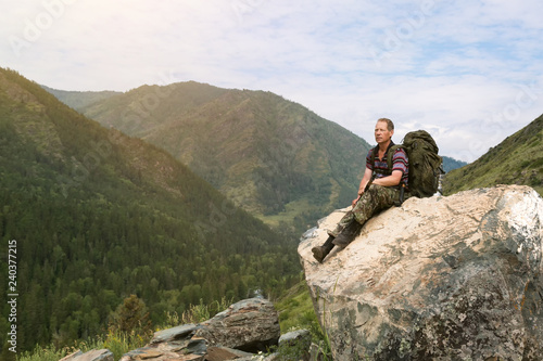 Foto  A tourist on a high mountain looks at nature