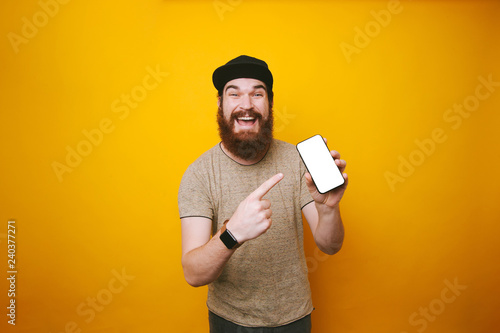 Fotografia  Happy young bearded man is pointing at white screen of smartphone