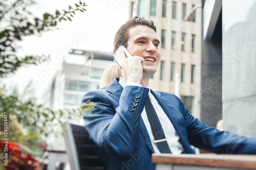 Young businessman talking by mobile phone in street cafe and looking straight Wallpaper Mural