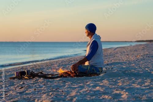 Fotografía  Traveler sits next to a bonfire on the seashore