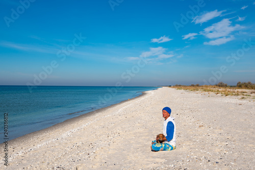 Fotografie, Obraz  Traveler with funny dog sits on the deserted beac