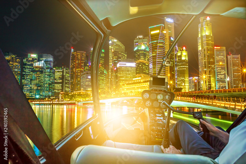 Foto op Aluminium Aziatische Plekken Helicopter cockpit on Singapore downtown skyline with skyscrapers of Business District and bridge in marina bay promenade. Scenic flight above Singapore with the lights of night reflects in the bay.