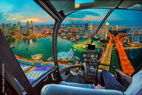 Helicopter cockpit interior on twilight panorama of Singapore marina bay with illuminated skyscrapers of the financial district in the downtown of the city. Singapore cityscape aerial view.