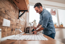 Low Angle Image Of Handsome Young Man Washing The Dishes In Modern Kitchen.