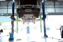 The Under View Of Grey Pick Up Car On Lift  At Service Bay Inside The Car Service Center With Blue Oil Tank At Bottom And Bright Daylight From Outside