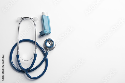 Asthma inhaler, stethoscope and space for text on white background, top view Canvas Print