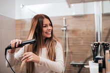 Beautiful Young Smiling Woman Using A Hair Straightener While Looking Into The Mirror In Bathroom.