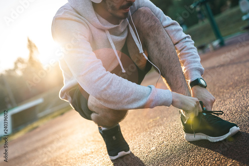 Fotografía  Young sportsman tying shoelace while crouching and listening to music in the mor