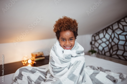 Photo Portrait of a smiling little mixed-race girl with blanket sitting on bed and looking at camera