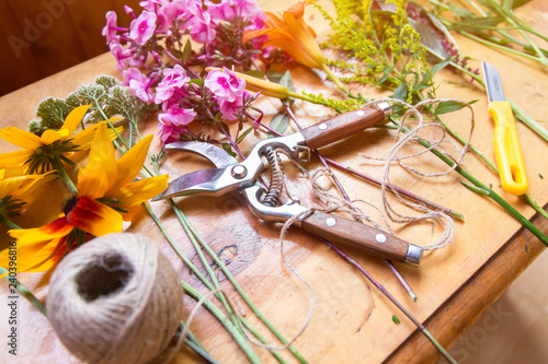 Florist workplace. Flowers and tools to create a bouquet on a table