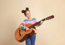 Cute Little Girl Playing Guitar On Color Background