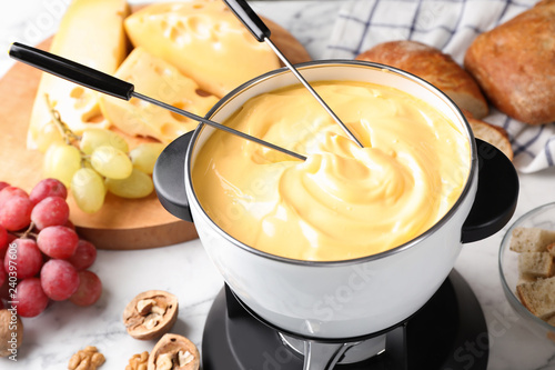 Pot of delicious cheese fondue and forks on table