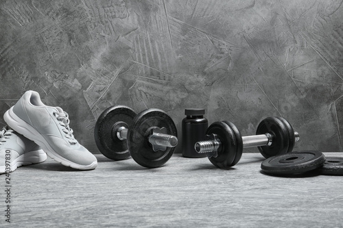 Composition with dumbbells and fitness accessories on floor Fototapeta