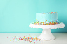 Fresh Delicious Birthday Cake On Stand Against Color Background. Space For Text