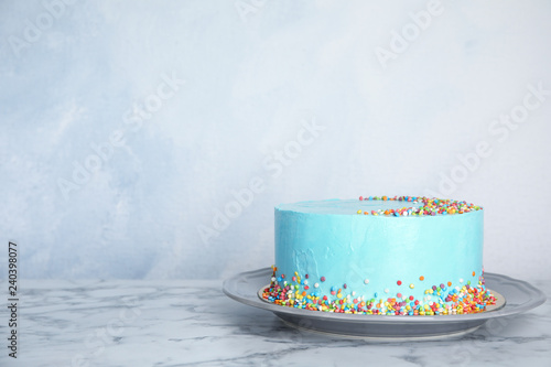 Plate with fresh delicious birthday cake on table against color background. Space for text