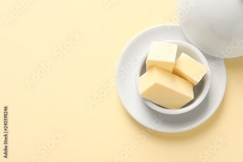 Photo  Dish with tasty fresh butter and space for text on color background, top view