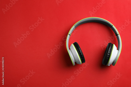 Wireless headphones on color background, top view. Space for text