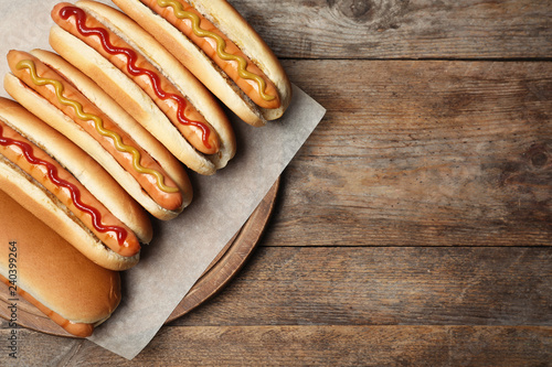 Tablou Canvas Tasty fresh hot dogs on wooden table, top view. Space for text