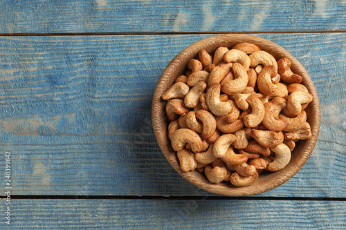 Tasty cashew nuts in bowl on color wooden table, top view. Space for text