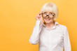 Leinwanddruck Bild - Joyful senior lady in glasses laughing isolated over yellow background. Friendly, mature white haired woman wearing glasses with a smile.