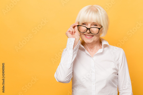 Fényképezés Joyful senior lady in glasses laughing isolated over yellow background