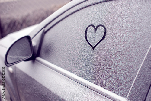 heart symbol on frozen car window in winter