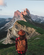 Young Traveler Girl With Backpack And Hat Standing On Mountains At Sunset.