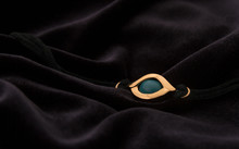 Golden Amulet Eye Pendant Bracelet On Velvet Dark Fabric