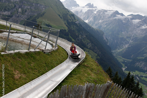 Photo  Mother and son sliding down an alpine coaster on vacation laughing