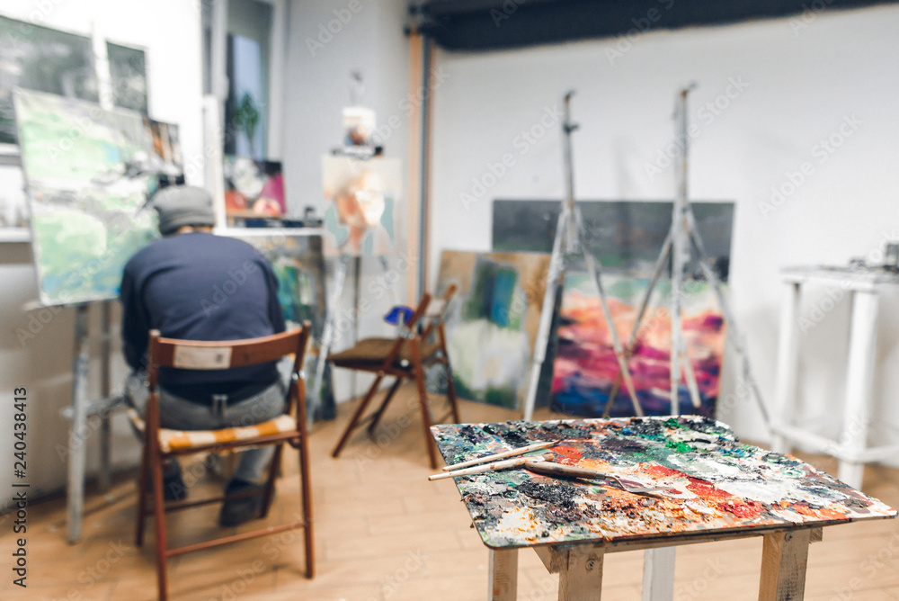 Fototapety, obrazy: Palette and brush stand on the background of a painter sitting on a chair and paints a picture at the hostel in a cozy studio. Studio of painting. Painting workshop