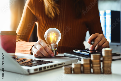 Obraz business man hand holding lightbulb with using smartphone and calculator to calculate and money stack. idea saving energy and accounting finance in morning light - fototapety do salonu