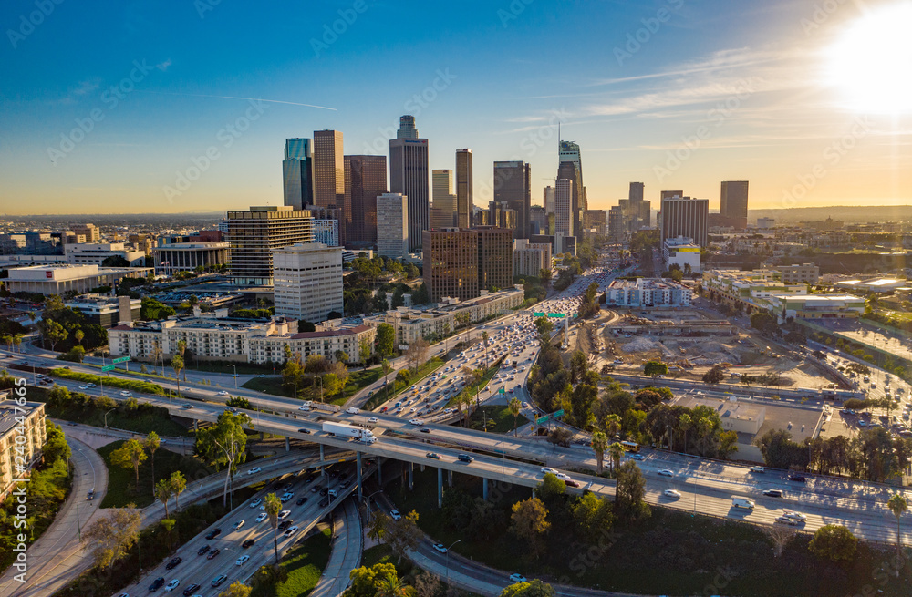 Fototapeta Drone view of downtown Los Angeles or LA skyline with skyscrapers and freeway traffic below.