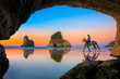 view from the cave of scenery view the sunset of Wharariki beach with Woman riding horse on the reflection beach, New zealand summer tourist popular place for vacation long weekend