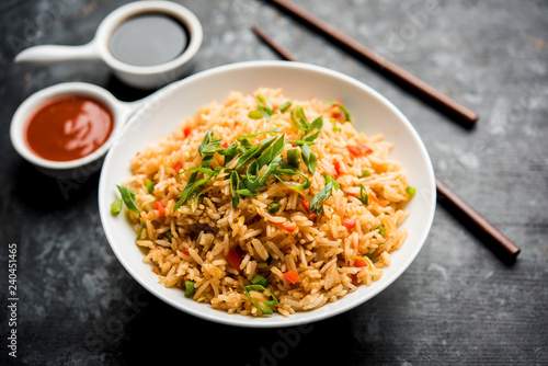Photo  Schezwan Fried Rice Masala is a popular indo-chinese food served in a plate or bowl with chopsticks