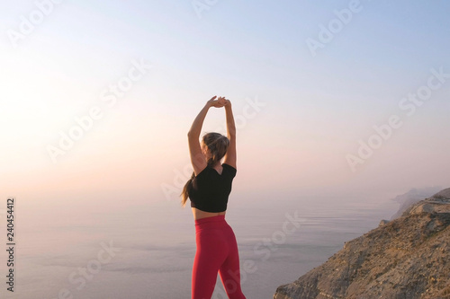 Photo  Beautiful view of woman doing yoga stretching on the mountain with sea view at sunset
