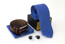 Brown Belt, Blue Tie With Box And Pocket Square, Pair Of Sapphire Cuff Links On White Glassy Surface. Fashion Concept