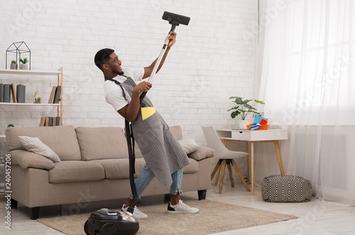 Fotografie, Tablou  Young man cleaning house with vacuum cleaner